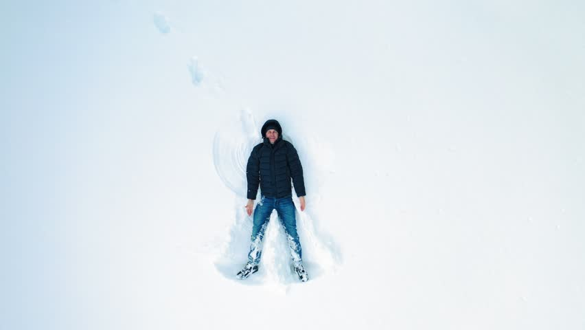High angle view of happy man lying on snow and creating snow angel figure