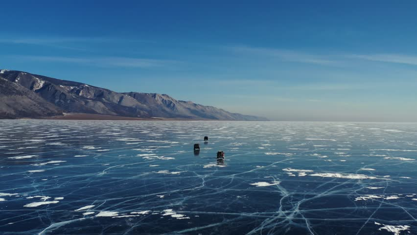 Aerial Perspective View of Cars Driving on Beautiful Deep Blue Ice Textured Frozen Baikal Lake Surface from above Captured with a Drone at Sunny Winter Day in Russia