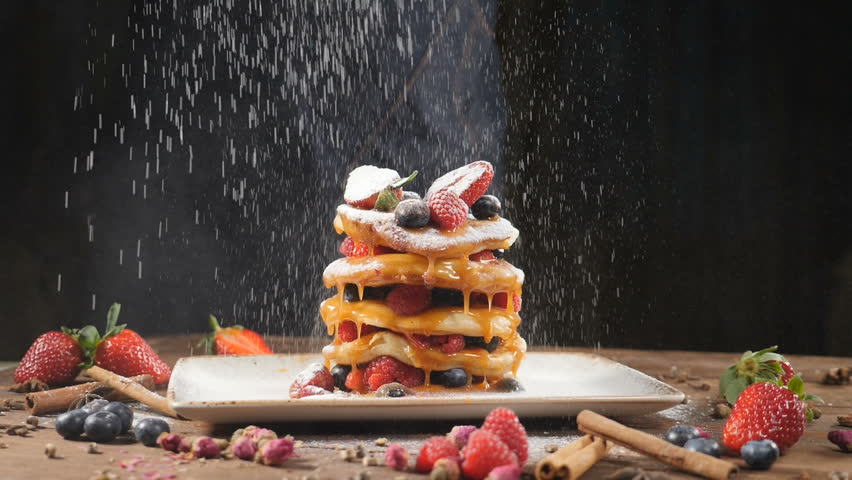 Sugar powder being poured over pancakes beautifully served with berries and caramel syrup. Food art. Dessert and breakfast concept. Closeup shot. pastry pour sugar. Slow motion. hd #1027972814