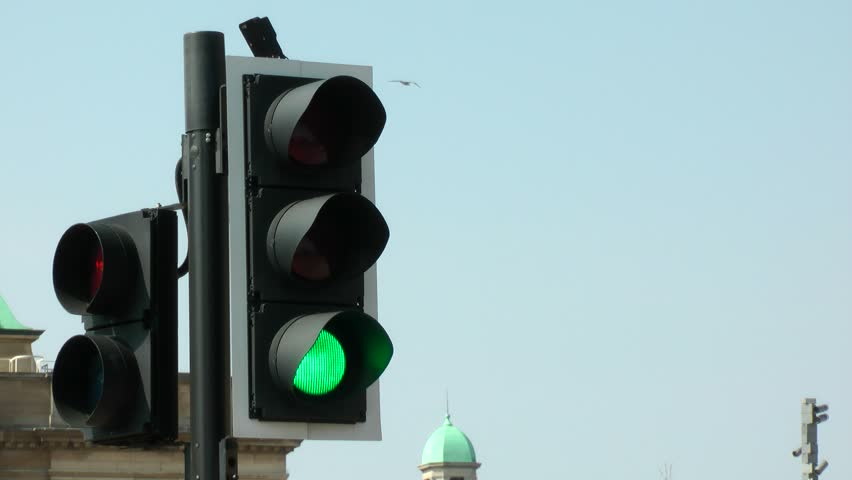 UK road crossing traffic lights from red, amber, green. filmed In busy city street. Medium shot.