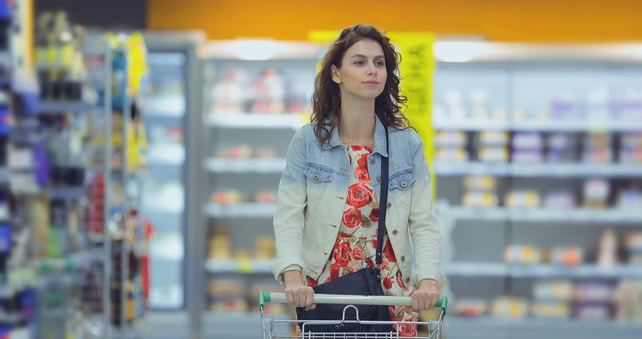 Pretty young woman walks through the supermarket hall with a cart and smiles. Girl chooses goods in the store and carries a trolley.