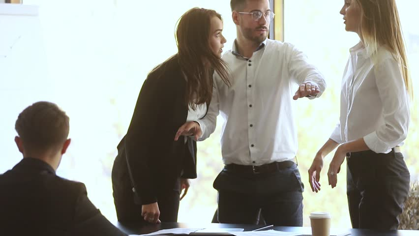 Male colleague set apart angry business women coworkers argue about mistake in papers fight at corporate office meeting, mad female employees clients quarreling shouting conflict at workplace concept