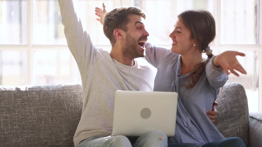 Excited happy young family couple looking at laptop computer feel winners surprised by lottery betting winning bid, celebrate good internet news embracing overjoyed by victory achievement online