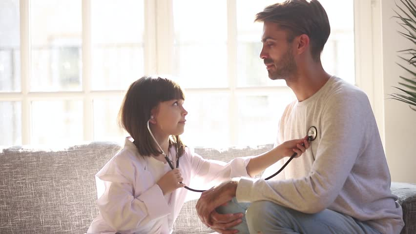 Cute small child daughter dressed in white coat holding stethoscope listening to father patient at home, funny little kid girl playing game as doctor pretending nurse having fun with dad sit on sofa #1028009591