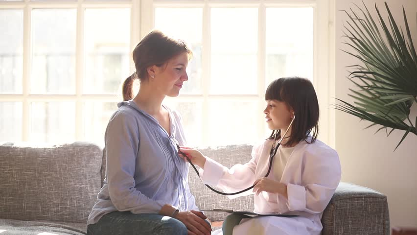Little funny kid girl dressed in medical uniform playing as doctor with mom at home, cute small child daughter pretending nurse holding stethoscope listening to mother chest having fun sit on sofa