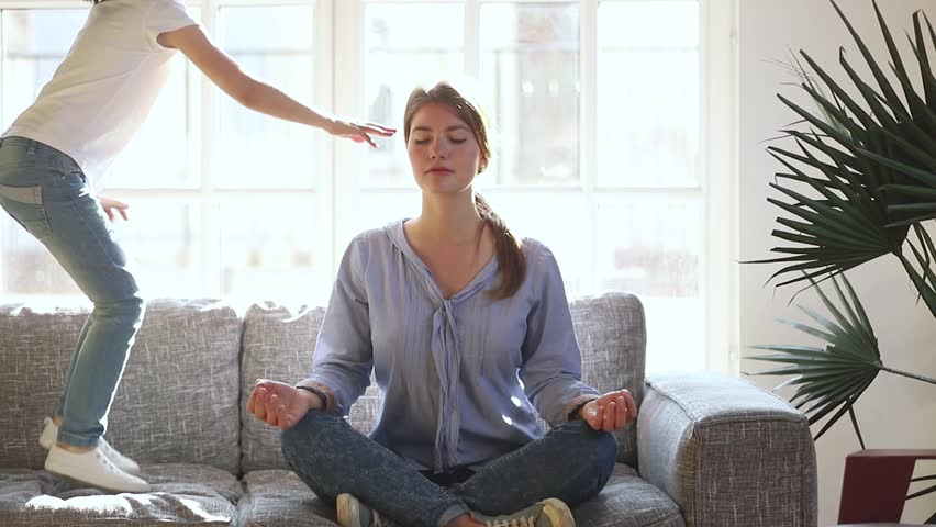 Mindful single mother meditating sitting on sofa while active energetic child daughter jumping playing, calm young mom doing yoga exercise at home for stress relief relaxing with naughty little kid #1028009603