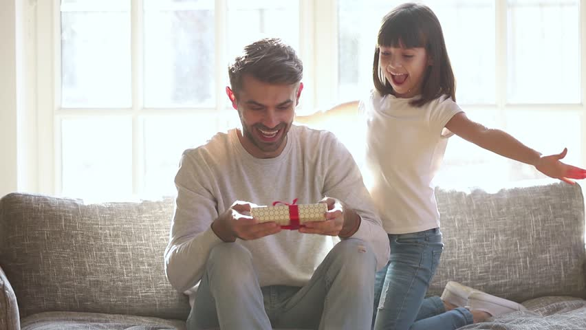 Cute kid daughter make surprise present covering eyes of happy dad receive gift box sit on sofa, little child girl congratulating parent smiling excited daddy on fathers day birthday embrace at home  Royalty-Free Stock Footage #1028009654