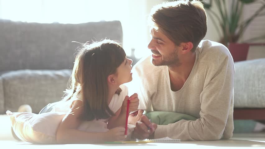 Loving dad and little kid daughter draw with pencils laying on warm floor in living room lit with sunlight, father coloring picture with child girl talk at home enjoy creative activity play together