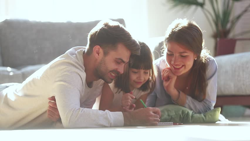 Happy family young parents drawing coloring picture with pencils helping cute child daughter enjoying talk play laying on warm floor at home, mom dad and kid girl having fun in living room on leisure #1028009672