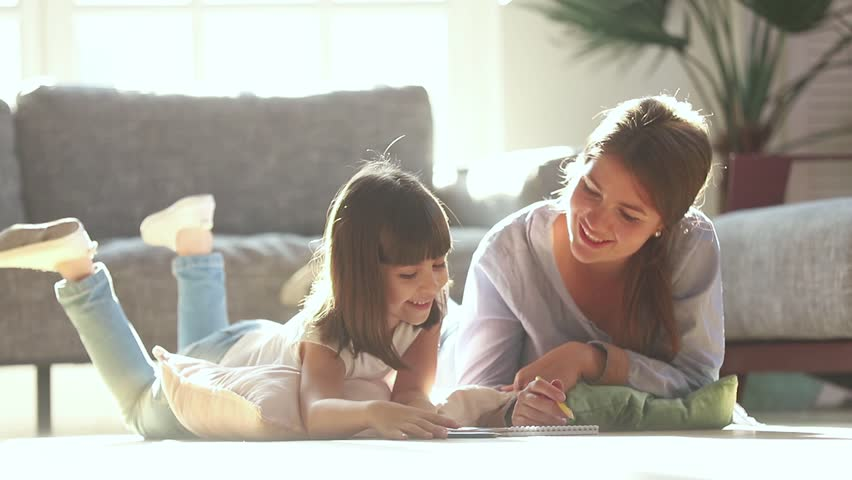 Happy family mother baby sitter teaching cute child girl playing on warm floor at home, mom helping kid daughter learning drawing coloring with pencils together enjoy creative activity in living room