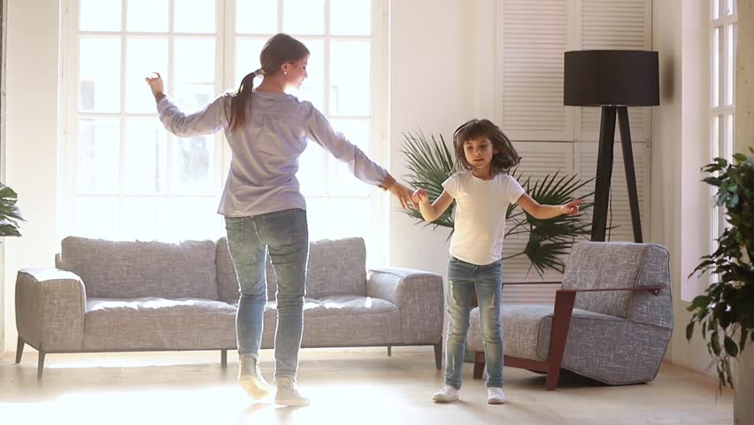 Active young mom babysiter and cute little kid daughter jumping dancing in modern house living room, happy family mother with child girl having fun enjoy playing funny activity together at home #1028009684