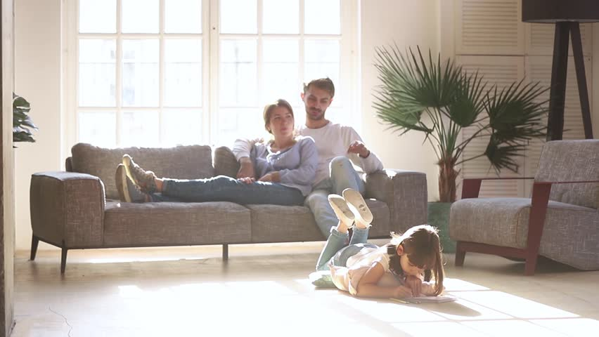 Happy family leisure at home concept, couple parents relaxing talking on sofa couch in comfort living room lit with light while little kid child daughter enjoy activity playing drawing on warm floor #1028009687