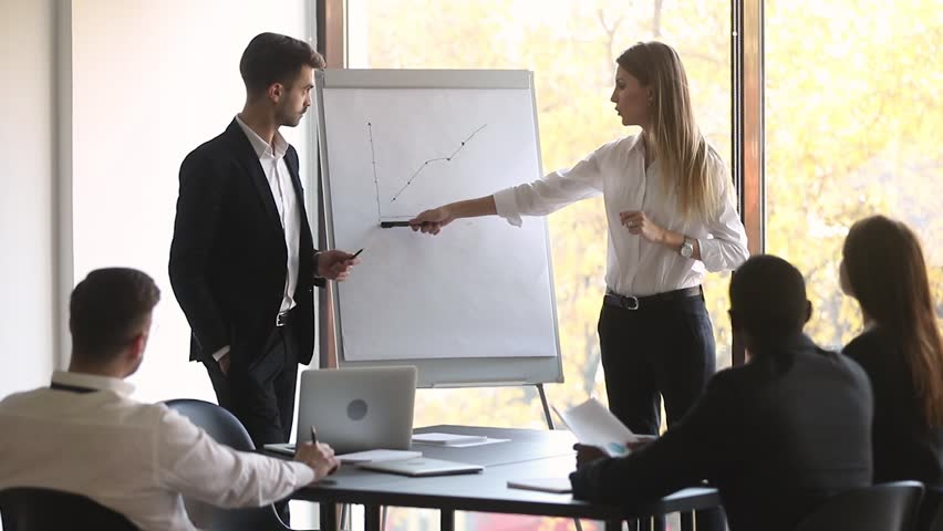 Two professional business coaches company leaders teachers give flip chart presentation explain graph consult clients training workers group at conference meeting office team workshop in boardroom