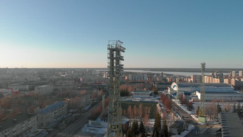 Open stadium in the winter, a tower with spotlights, aerial shooting from the copter | Shutterstock HD Video #1028014475