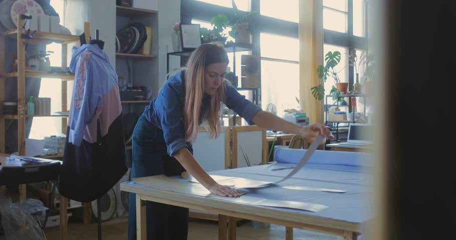Young woman cutting fabric by edge of paper pattern while making new item for seasonal fashion collection | Shutterstock HD Video #1028015660