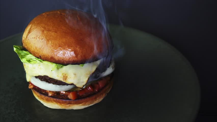 Fresh smoky appetizing cheeseburger rotating in 4k. | Shutterstock HD Video #1028018762