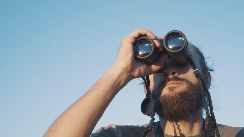 A bearded masculin man in military t-shirt looks through binoculars. Concept: new horizons, development, travel, territory explorer, adventure time, birdwatching, hunting. close up   Shutterstock HD Video #1028020952