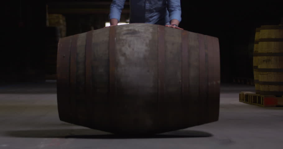 Large whiskey sherry barrel keg rolling toward camera slow motion