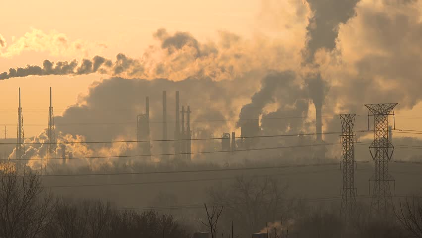 Smokestacks from an oil refinery in the morning sunlight spewing out hazardous polluting fumes causing global warming Royalty-Free Stock Footage #1028048900