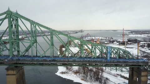 Cinematic drone / aerial footageing sideways showing cars on Jacques Cartier Bridge and in Montreal, Quebec, Canada during winter season.