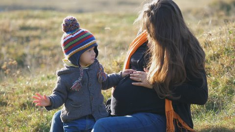 Portrait of little child caress and embrace pregnant mother belly outdoor, happy mom dream, boy hearing the sound of life, innocent love