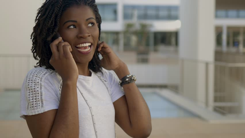 Smiling African American woman talking on phone. Cheerful young lady with dreadlocks having pleasant conversation through phone. Communication and technology concept | Shutterstock HD Video #1028082572