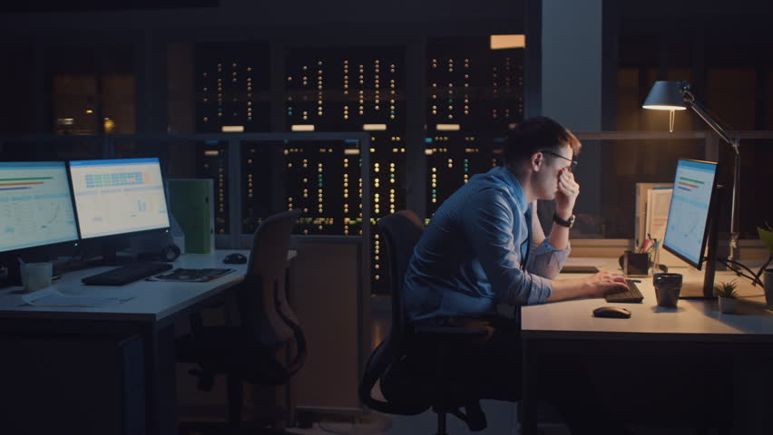 In the Office at Night, Overworked Tired Office Worker Uses Desktop Computer but Falls Asleep Fast. Tired Frustrated Exhausted Businessman Falls asleep at His Job | Shutterstock HD Video #1028084255