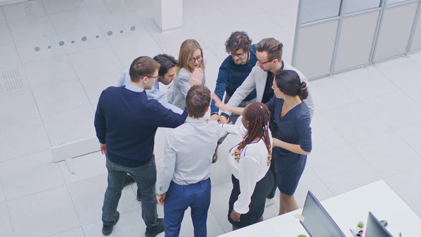 Office Workers doing Team Building Exercise Stacking Hands Together in the Unifying Spirit of Creativity and Common Cause. Eight Successful People Applauding Together. High Angle Shot in Modern Office Royalty-Free Stock Footage #1028085821