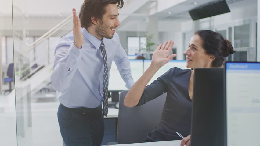 Two Professional Office Workers Work on Desktop Computer, Together Find Solution to a Problem and Cheerfully Celebrate Success by Doing High Five. Diverse Team of Beautiful People in Open Space Office