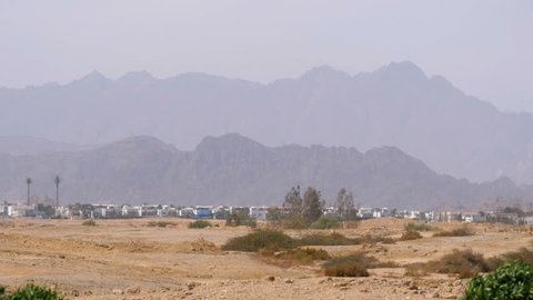 Panoramic view of buildings and houses in the desert mountains in the background in Egypt. Sharm el Sheikh. Mirage, hot weather, evaporation. Hot desert, heat.