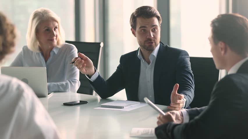 Businessman in suit talking to business people colleagues or partners sitting at conference table, male leader discussing work at team meeting or group negotiations having conversation with clients