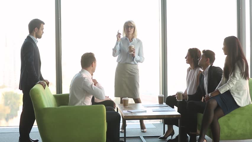 Friendly female mature old leader talking to diverse workers clients group at coffee break, business people team colleagues having fun conversation with middle aged boss discussing work in office