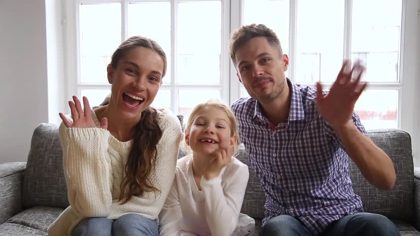 Happy family with little daughter sitting on couch at home waving hands look at camera talking at webcam say hello greeting friend or relatives, vloggers makes online video call recording vlog concept
