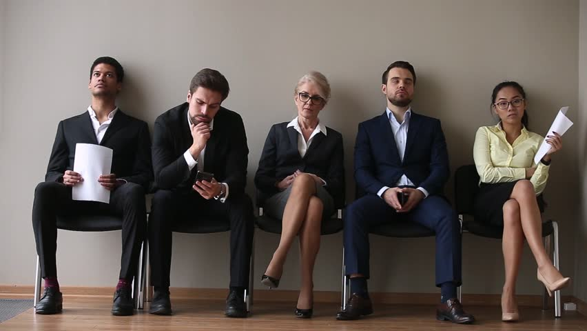 Different ages and ethnicity candidates for vacancy sits on chairs in queue corridor feels nervous bored waits job interview turn, business people holds phones cv papers, recruitment hiring hr concept | Shutterstock HD Video #1028104295