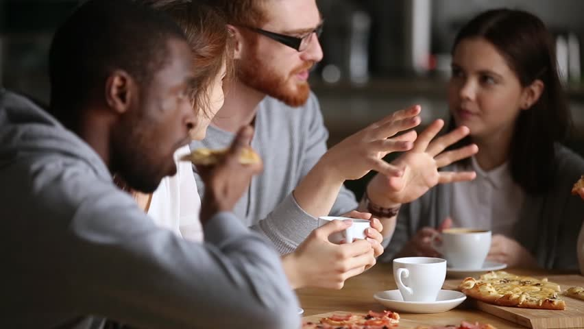 Millennial multinational friends students or colleagues gathered in cafe or pizzeria during lunch chatting enjoy conversation eating pizza drinking coffee or tea, group listens redhead guy share news