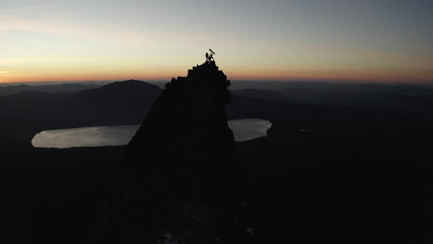 People standing on top of a mountain peak in Oregon with an American Flag