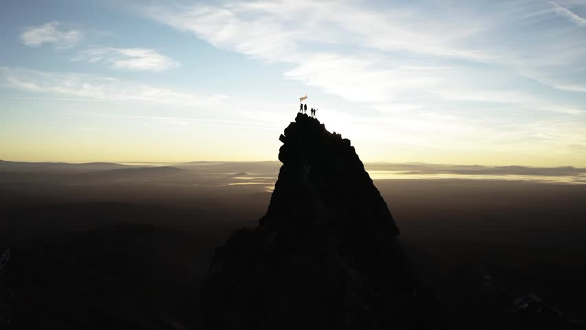 People standing on the needle nose face of a HUGE mountain peak in Oregon