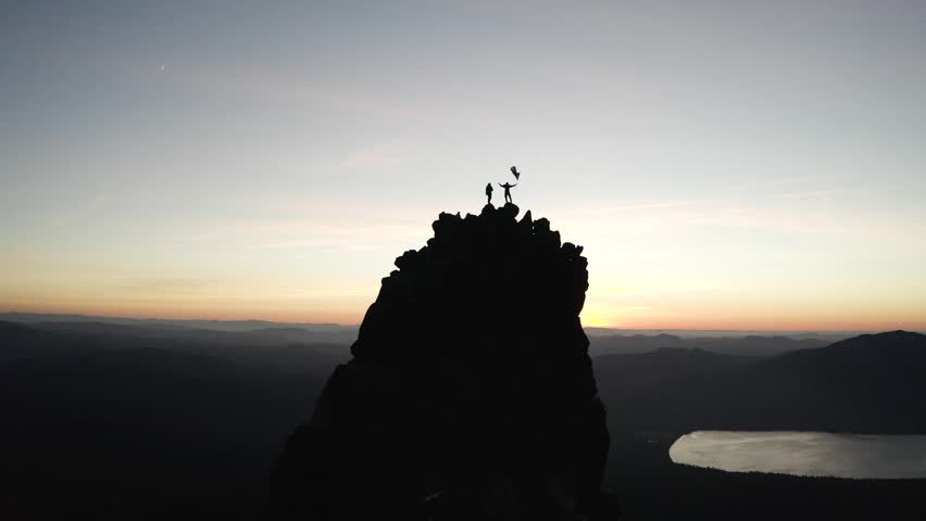 Men standing on a tall mountain peak in Oregon with an American Flag