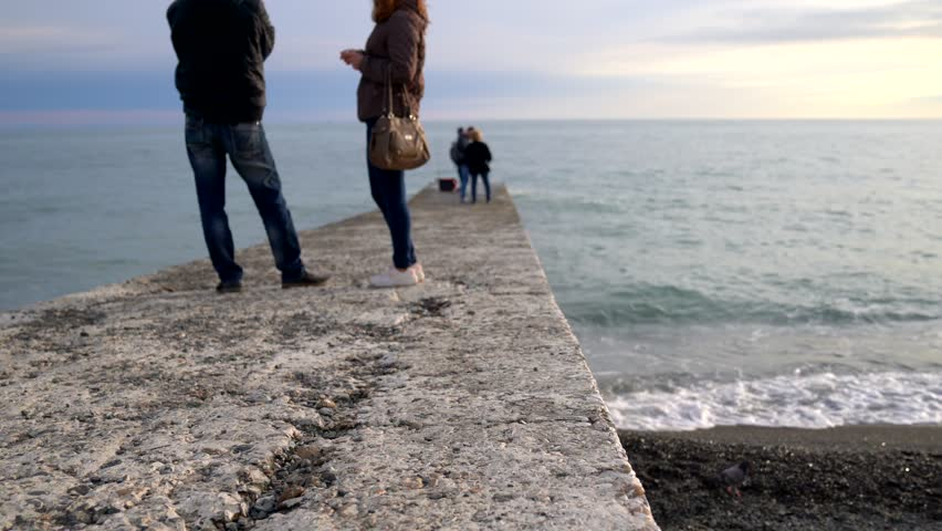 Stone / concrete boardwalk with pigeons and a talking couple at the Black Sea in Sochi, Russia at beautiful sunset | Shutterstock HD Video #1028110631