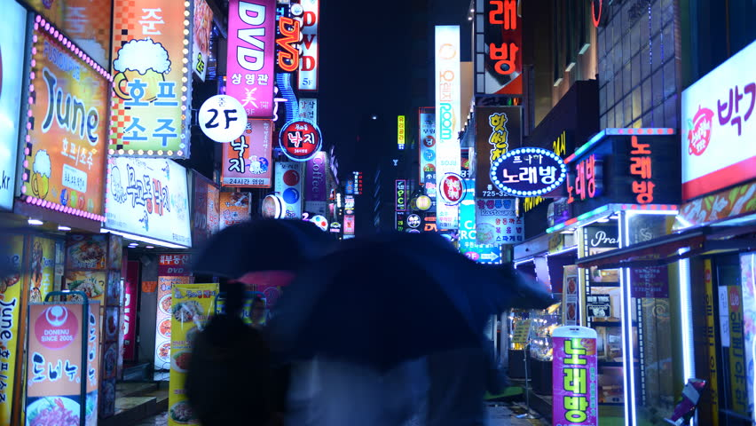SEOUL, SOUTH KOREA - APRIL 16, 2012 Time Lapse of Seoul City Crowd of People Visit Busy Shopping Street Rainy Night
