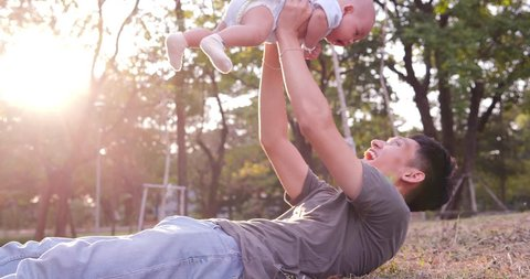 Father playing with baby at park. Father holding baby in hand and playing together with happy emotion.