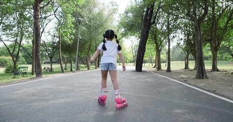 Asian little girl playing roller blade on the road at park. concept of activity holiday, learning development and life experience. 4K resolution and slow motion.