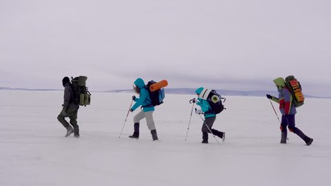Side view shot of a group of sportsmen trekking in winter.