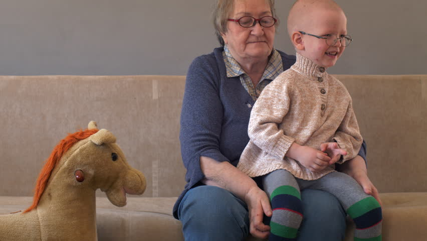 Elderly woman sits and plays with her grandson on couch. Child is very fond of grandmother. Boy kiss and hug his beloved grandmother. Kid shows him playing on rocking horse. | Shutterstock HD Video #1028133224