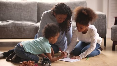 African mother and little kids mixed race son daughter sitting on warm floor drawing use colorful pencils spend free time together at home, leisure or hobby, underfloor heating modern dwelling concept