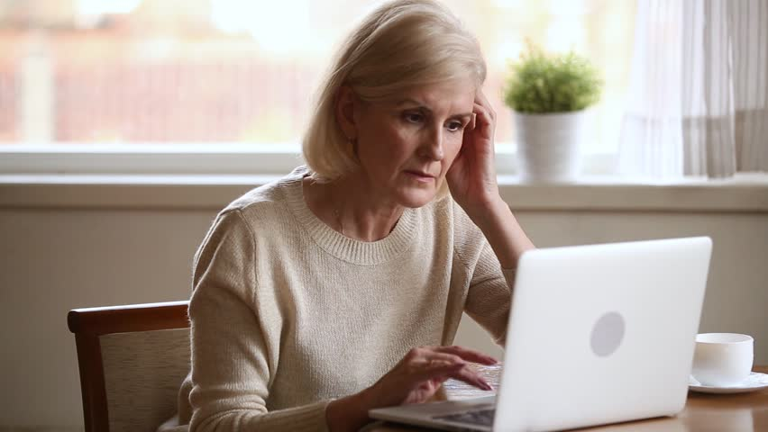 Serious elderly woman sitting at table in kitchen typing e-mail on computer working at home, aged user search information, browse internet website, use app online banking, communicating online concept