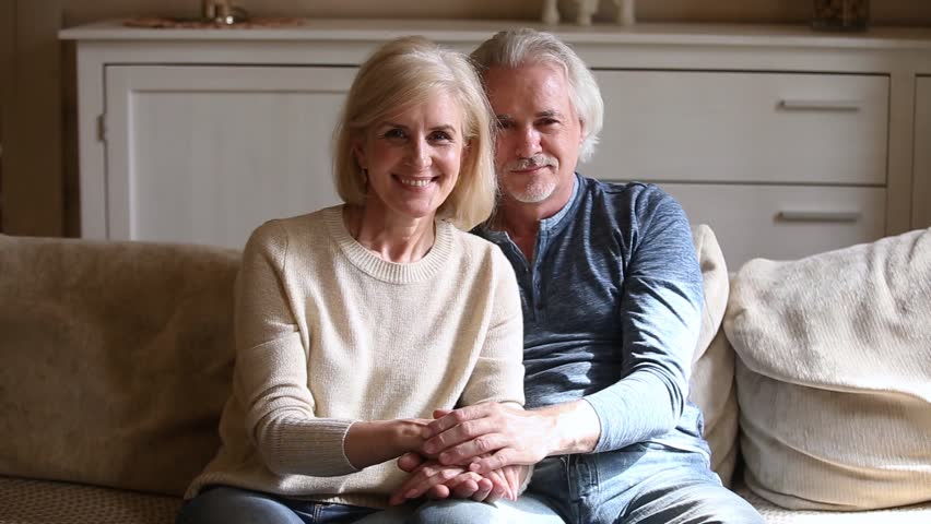 Grey haired elderly couple in love sitting on couch holds hands looking at camera feels happy, mature loving spouses indoors, healthy retirees resting at modern home enjoy time with each other concept Royalty-Free Stock Footage #1028137091