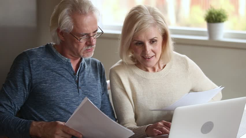 Elderly couple holds bills makes online payment use pc, check bank account balance feels satisfied, wife explains help to husband do transaction, easy secure money remittance modern tech usage concept Royalty-Free Stock Footage #1028137106