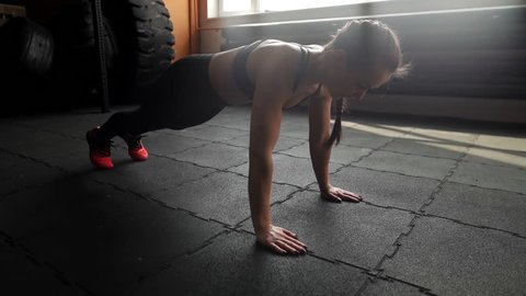Athletic beautiful woman doing push-ups on the floor in slow motion in the gym. Sexy sporty girl trains triceps and her back on the floor with black mats and repeats 4 times. Camera moves horizontally