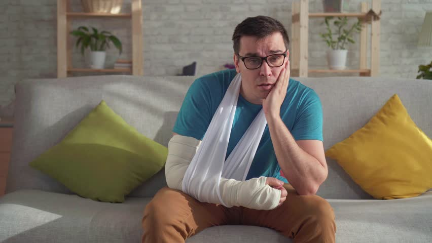Sad young man in glasses with broken arm
